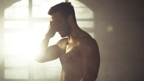 Handsome Shirtless Man with Naked Muscular Torso with Visible Six Pack Stands Resting after Bodybuilding Exercise, He Wipes Sweat from His Forehead. He's in the Middle of Abandoned Factory Building.