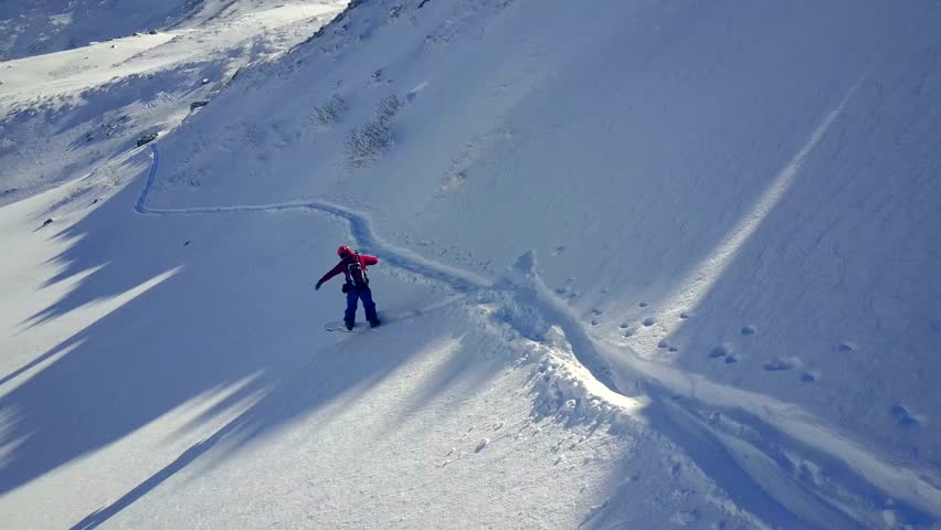 Incredible 4k aerial drone camera view on lonely professional snowboarder riding downhill in snowy mountain landscape | Shutterstock HD Video #29875831