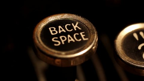 """A male finger presses the """"backspace"""" key on an old typewriter."""