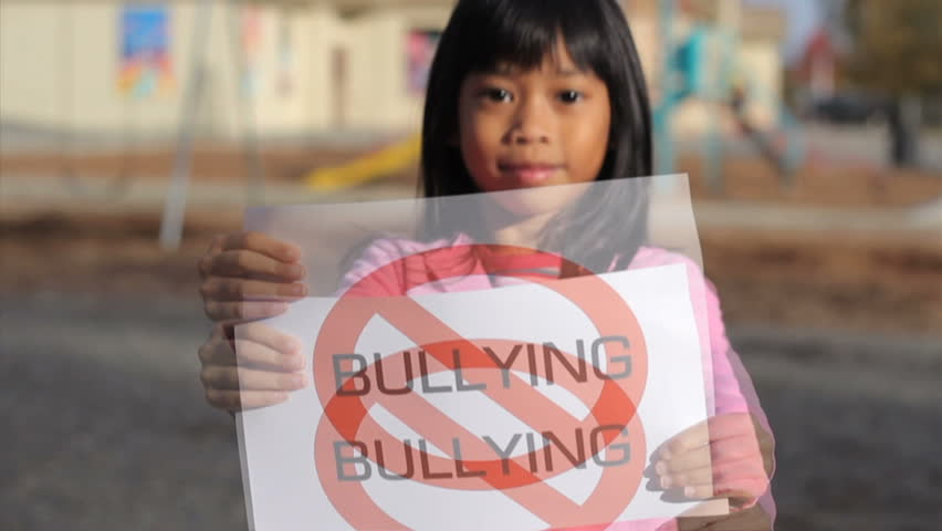 "A cute Asian girl holds up a large ""NO BULLYING"" sign on the school playground."
