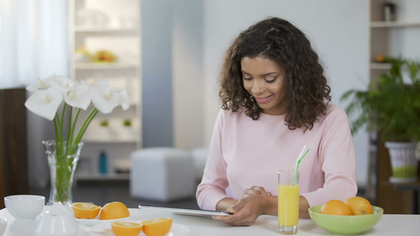 Mixed race young woman reading article on tablet, body care and nutrition | Shutterstock HD Video #29900719