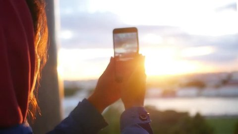 Shoot a panorama of an evening city with a sunset on the phone. slow motion, 1920x1080, full hd
