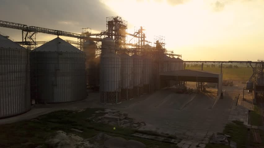 Flight under granaries and elevators or oil storage on sunset