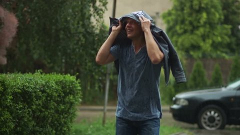 Portrait of Handsome Man in Blue Shirt Hiding His Head from the Rain under the Jacket.