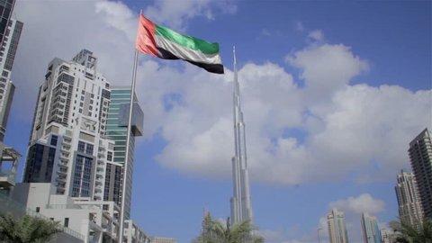United Arab Emirates national flag waving against the Burj Khalifa Building, Dubai, UAE