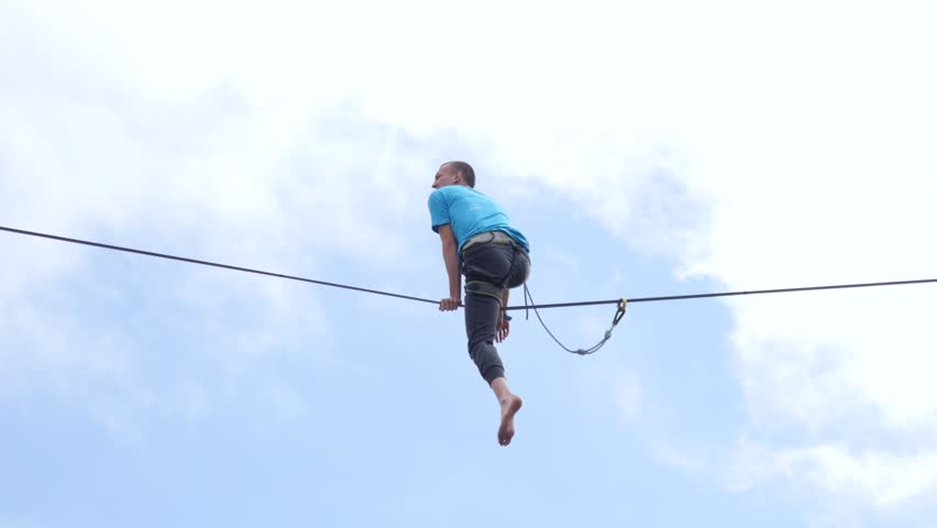OLESNICA near WROCLAW, POLAND - AUG 12, 2017: Free open air street circus busker festival. Trick Walking On A Tightrope A Guy Acrobat Breaks Falls Down