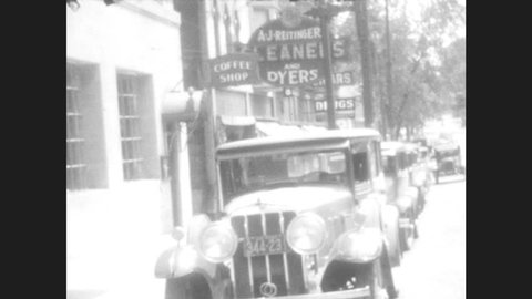 1920s: Woman and girl walk to car. Hotel Freeport. Car going down road lined with trees. Car going down street with streetcar and pedestrian crossing street. Car drives around curve and down hill.