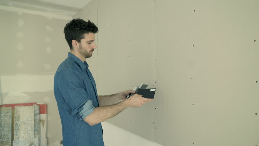 Young man checking, trying paint from palette on wall for his new home  | Shutterstock HD Video #29965321
