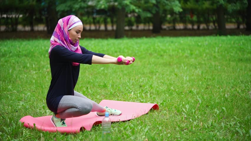 A modern Muslim woman who clothed a veil over her head is engaged in sports on a summer day in the park, the lady does exercises to strengthen the leg muscles and stretch the back of the thigh