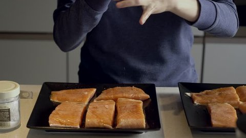 A young woman is cooking salmon fish, served on black plates