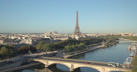 Aerial view of the Eiffel Tower at sunrise with bridge in front, over the river at sunrise in Paris, 4K. Vue aérienne de la Tour Eiffel au matin, au dessus du pont, le long de la Seine à paris, 4K.
