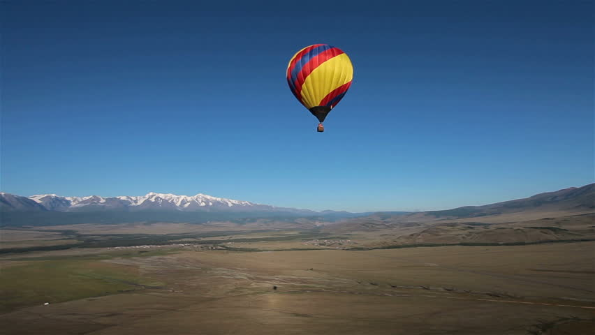 Hot Air Balloon flying across the sky in mountain landscape, Altai, Siberia. Landscape panorama. Aerial view.