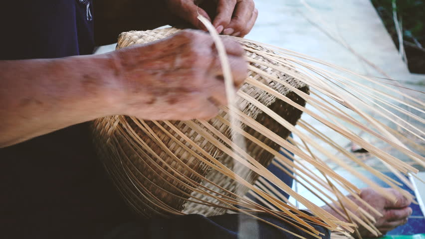 Hands weaving bamboo basket, handmade by Villagers from Chiangmai, Thailand.