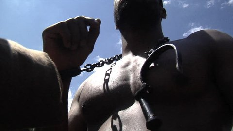 VIRGINIA - 2016. Re-enactment recreation of 1700-1800s Southern American Slavery, slave era. Enslaved African-American. Laboring in bondage with hands in chains, tattered clothing, Field slave.