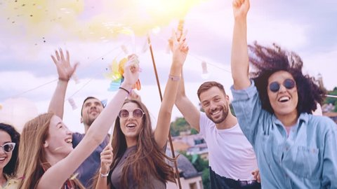 Diverse Group Of Young Hipsters Friends On Rooftop Lifting Up Sparkler Fire In The Air In Colorful Smoke Laughing And Dancing In Confetti Beautiful Youth Festive Time Happy Event Concept At Dusk Shot