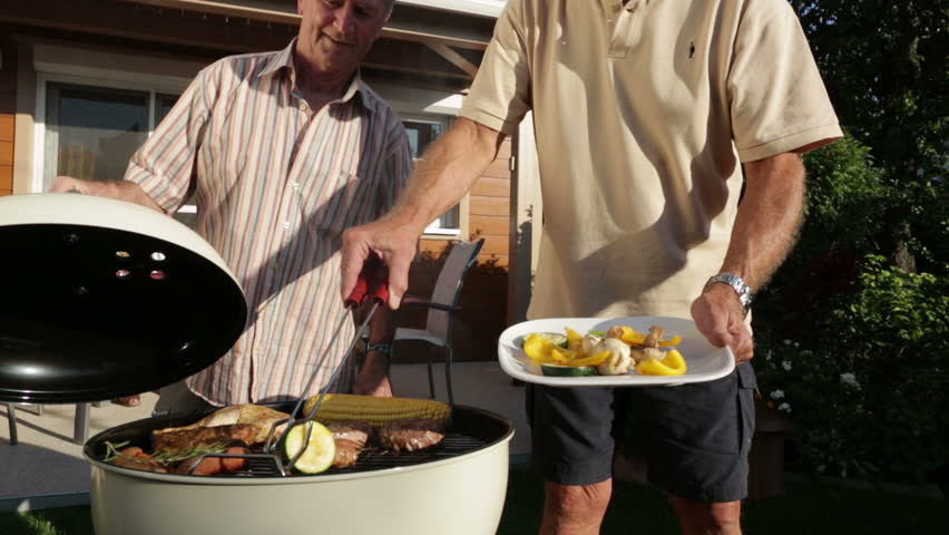 retirees cooking on kettle barbecue in garden
