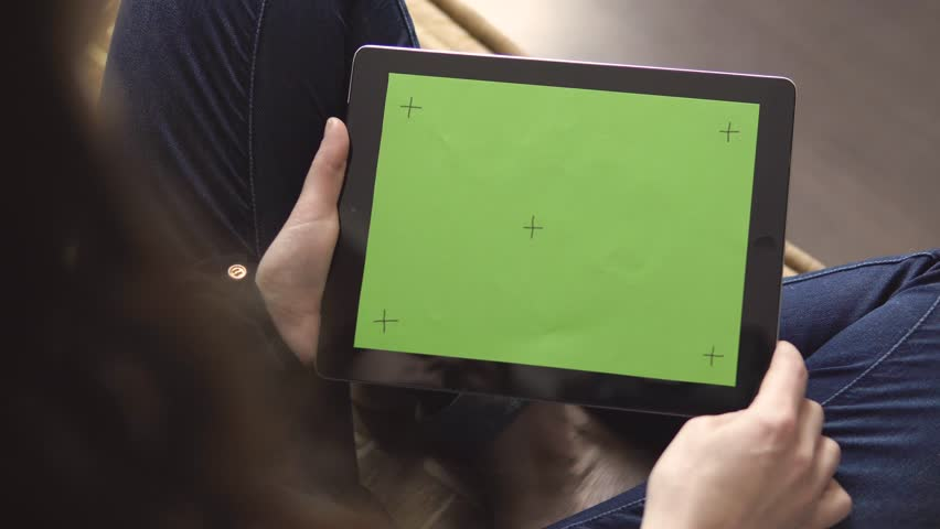 Girl sitting on brown sofa is holding a tablet pc with green screen and markers, making pick gestures on touchpad, 4K | Shutterstock HD Video #30017401