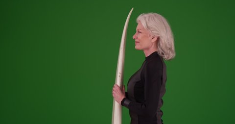 Profile of attractive senior woman holding surfboard on greenscreen. Cheerful elder female ready to surf on green screen to be keyed or composited.