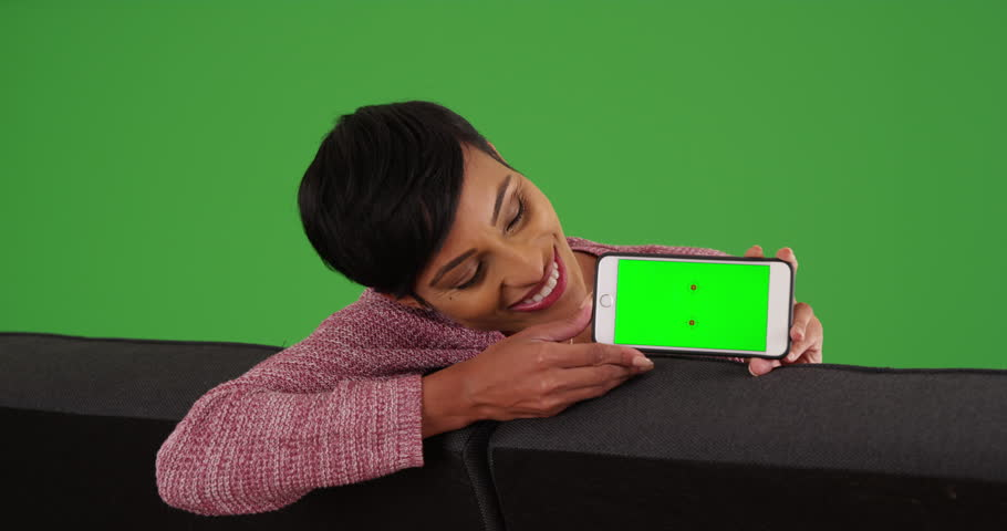 Portrait of smiling black female sitting on couch holding smart phone with green screen on green screen. On green screen to be keyed or composited. #30030511
