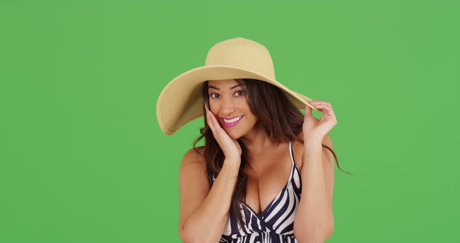 Smiling Latina female modeling sunhat on green screen. On green screen to be keyed or composited.