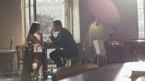 Romantic couple man and woman sitting at a cafe table. Loving couple man and woman drinking coffee in a cafe near an open balcony. View happy couple talking in a cafe during day