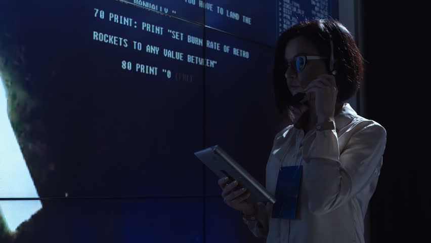 Side view of woman working at computer in space mission control center. Controlling the orbiting international space station ISS. Elements of this image furnished by NASA.