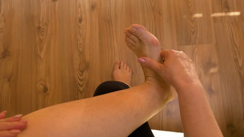 Point of view of mature woman rubbing her sore and painful foot and toes doing herself massage therapy
