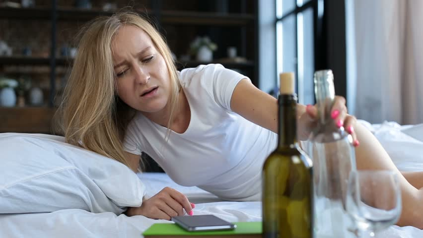 Boozy young woman waking up in bed after party