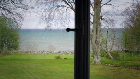 Seaview from house. Room with a view from window over a green garden and the sea.Camera travel.