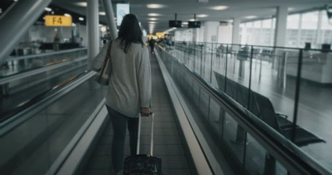 Woman using an airport walkway with suitcase in tow. (No discernible faces, all logos and trademark removed in post)