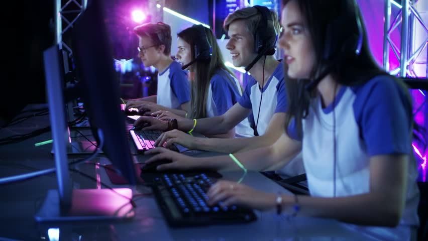 Moving Shot of Team of Teenage Gamers Playing in Multiplayer PC Video Game on a eSport Tournament. They Speak into Microphones Emotionally Charged Moment.