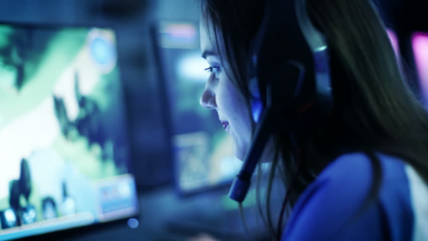 Professional Girl Gamer Plays in MMORPG/ Strategy Video Game on Her Computer. She's Participating in Online Cyber Games Tournament, or in Internet Cafe. She Wears Gaming Headphones. 4K UHD. | Shutterstock HD Video #30057832