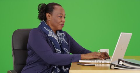 An African American businesswoman uses her mobile phone at her desk on green screen. On green screen to be keyed or composited.
