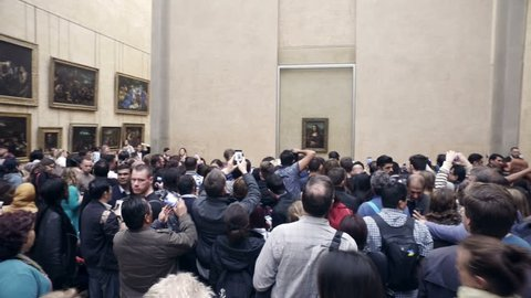 "PARIS, FRANCE - circa JUN, 2017: Visitors take photos near Leonardo DaVinci's ""Mona Lisa"" at the Louvre Museum in Paris, France. The painting is one of the world's most famous works of art."