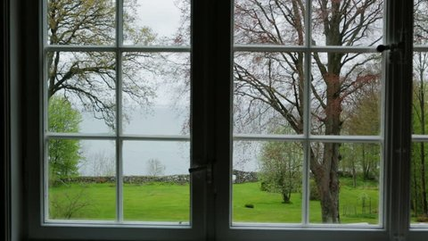 View from old summerhouse. Framed window Beautiful view over garden and sea. Camera travel left to right with slight pan,