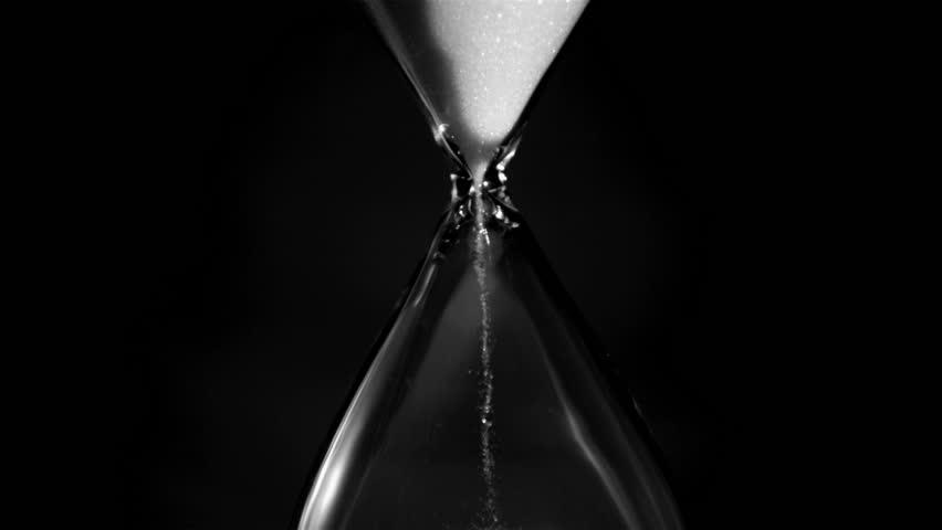Egg timer in super slow motion emptying against a black background