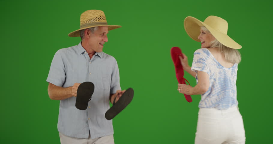 Two old white people dance around with their flip flops on green screen. On green screen to be keyed or composited.