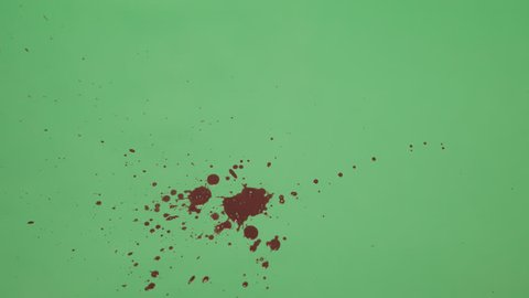 Red ink splatter over green screen background. Close-up shot