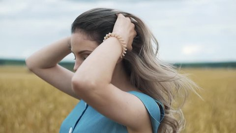 A young girl in a blue dress is standing in the field, and the wind is fluttering her hair
