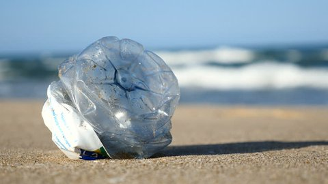 Marine pollution, a plastic bottle on a beach in Valencia, Spain. Filmed in August 2017.