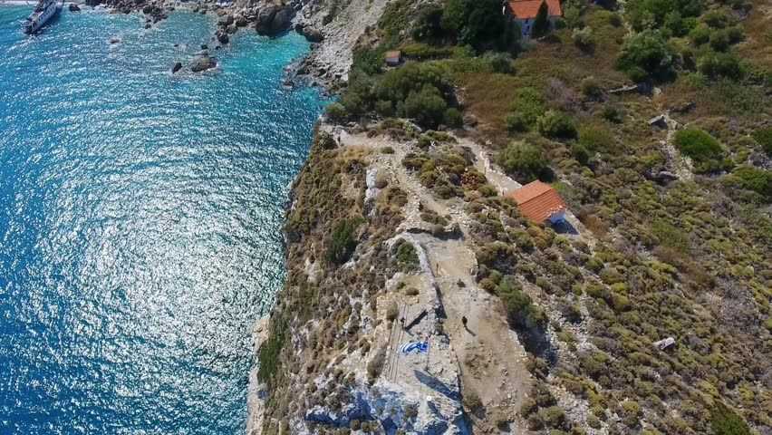 Aerial footage of the famous historical Kastro old town and beach on the Skiathos island in the Aegean sea in Greece.