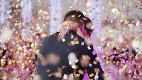 Young beautiful bride and groom dancing first dance at the wedding party shrouded by confetti. Wedding bouquet. Feel happy.