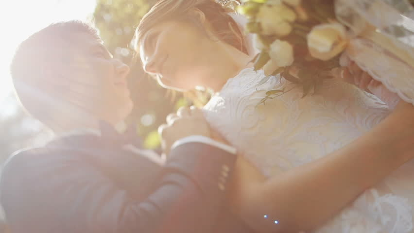 Young beautiful bride and groom hug and talk in the park. Wedding bouquet. Feel happy. The sun shines