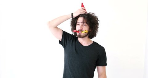 Man having fun while playing with party blowers