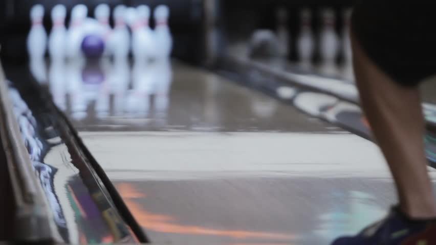 Abstract view of man throwing bowling ball strike down lane