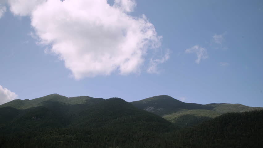 Cloud floats through blue skies above the Adirondack mountains.