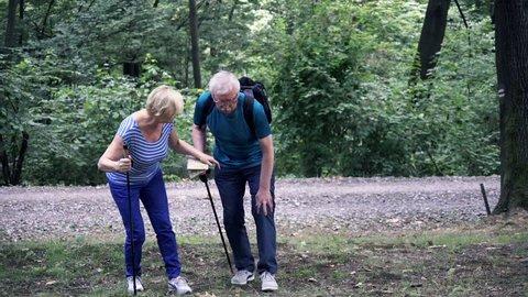 Senior man having injury after hiking in the park
