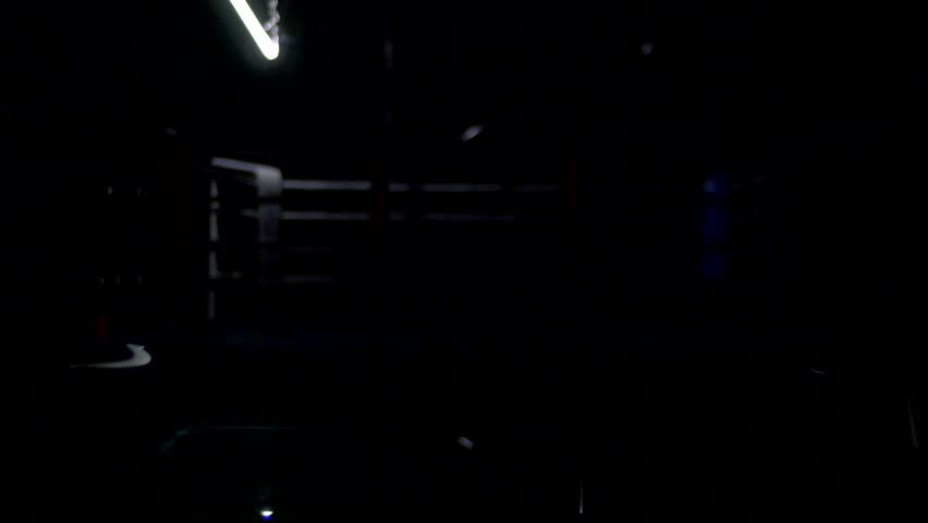 Boxing ring and two chairs with table dark background. View of a regular boxing ring surrounded by blue ropes spotlit by a spotlight. Light show around the boxing ring.