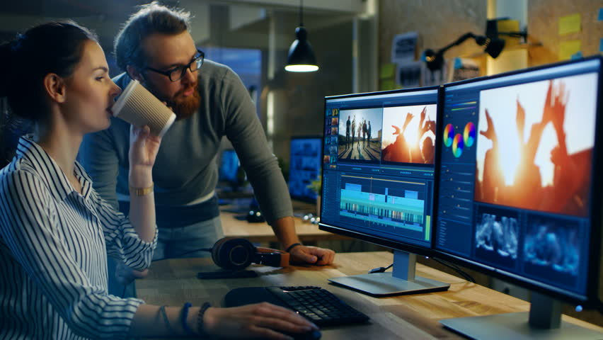 Female Video and Sound Editor Works With Her Male Colleague on a Project on Her Personal Computer with Two Displays. They Work in a Creative Loft Office. Shot on RED EPIC-W 8K Helium Cinema Camera.