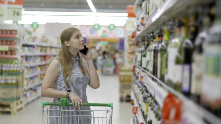 Blonde young and attractive woman walks the supermarket with a cart moving around the supermarket chooses alcohol. 4k. | Shutterstock HD Video #30254551